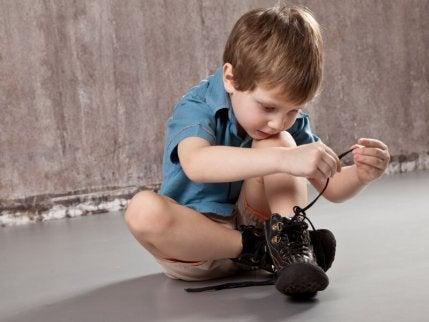 Niño atando cordones del zapato