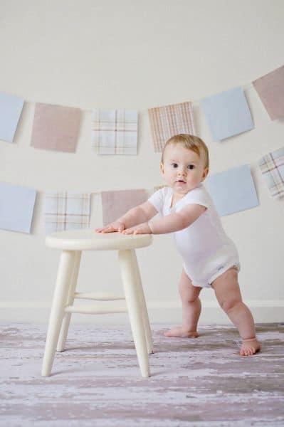 Bebé apoyado sobre un taburete