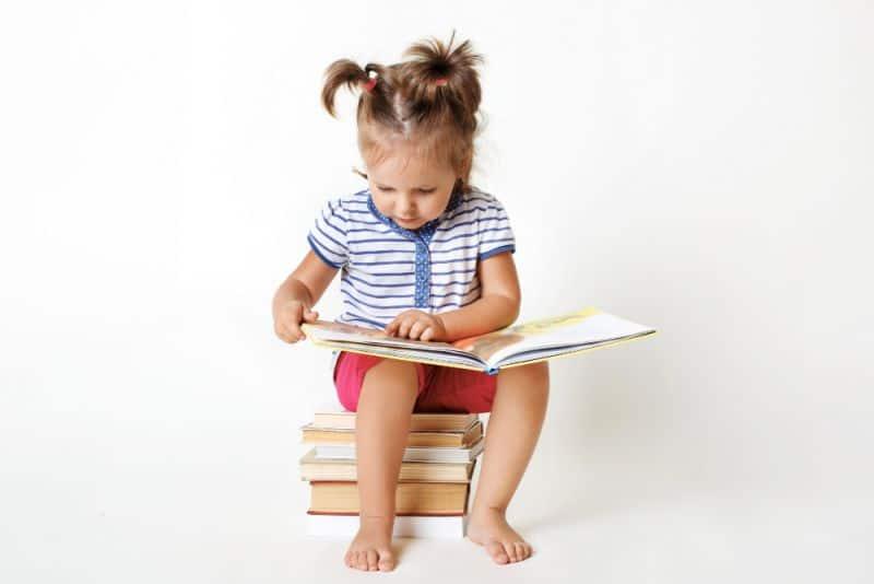 Niña aprende a escribir leyendo un libro