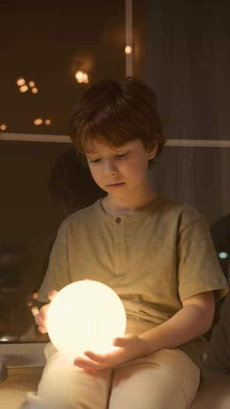 Niño sujeta luz LED que le ayuda a dormir solo por la noche