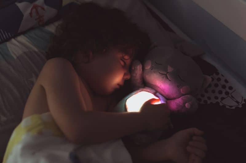 Niño dormido abrazado a su muñeco